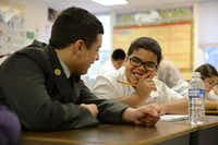 Bobby Carter, a freshman football player at North Dallas High School, helps fifth-grader Gustavo Martinez with a writing assignment at Onesimo Hernandez Elementary School. Bobby is part of the new Neighborhood Bulldogs program, which tutors and mentors students at the school's feeder elementary schools.( Staff photo by ROSE BACA )