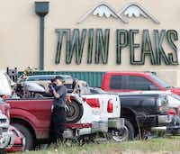 A law enforcement officer  photographed a vehicle in the parking lot of Twin Peaks in Waco last week. The shootout has put strains on McLennan County resources, and a judge is seeking help from public defenders in neighboring counties.(Jerry Larson - Herald)