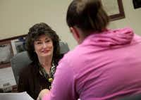 Kathy Severance, executive director at Lifeline Shelter for Families in Grand Prairie, talks with client Jennifer Alejo.Staff photo by BRAD LOPER