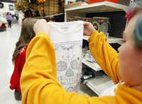 """Destiny Rucker  stocks Day of the Dead merchandise at Michaels in Mesquite. """"Michaels customers across the country are getting into   Day of the Dead decor,"""" says an executive.(Ben Torres - Special Contributor)"""