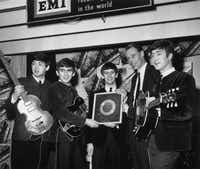 "On March 22, 1963, the Parlophone label (an EMI imprint) released the Beatles' debut album ""Please Please Me."" This photo, from April 8, 1963, shows the Beatles holding their silver disc."
