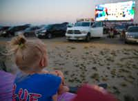 Layla Henderson, 4, of White Settlement, sits in the bed of her family's truck to watch the Lego Movie at the Texas Motor Speedway on Saturday, July 26, 2014.( Gregory Castillo  -  Staff Photo )