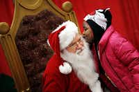 Ky'liah Ware whispered a wish to Santa Claus. Families lined up in the early morning hours on Saturday to enjoy a hot meal, haircut and other donated gifts.(G.J. McCarthy - Staff Photographer)