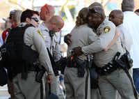 LAS VEGAS, NV - JUNE 08:  Las Vegas Metropolitan Police Department officers hug near a Wal-Mart on June 8, 2014 in Las Vegas, Nevada. Two officers were reported shot and killed by two assailants at a pizza restaurant near the Wal-mart. The two suspects then reportedly went into the Wal-Mart where they killed a third person before killing themselves.  (Photo by Ethan Miller/Getty Images)Ethan Miller - Getty Images