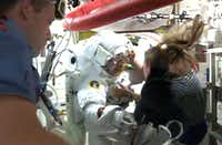 This July 16, 2013 NASA TV image shows International Space Station Italian astronaut Luca Parmitano being assisted back into the safety of the station by his fellow astronauts after experiencing problems with his spacesuit. Parmitano had a leak in his helmet while on a spacewalk outside the International Space Station Tuesday, forcing an early end to the outing, NASA said. NASA is probing whether the leak may have come from the liquid cooling ventilation system in the spacesuit, which contains about a gallon of water treated with iodine and may have a bad taste like Parmitano described.(HO/AFP/Getty Images - AFP PHOTO / NASA TV / NO SALES / NO MARKETING / NO ADVERTISING CAMPAIGNS / DISTRIBUTED AS A SERVICE TO CLIENTS)