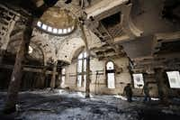 Coptic Christians walk amid debris inside Amba Moussa Coptic church in Minya.