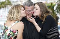 """(FILES) - A file picture taken on May 23, 2013 shows French actresses Lea Seydoux (L) and Adele Exarchopoulos kissing French-Tunisian director Abdellatif Kechiche as they pose during a photocall for the film """"Blue is the Warmest Colour"""" presented in Competition at the 66th edition of the Cannes Film Festival in Cannes."""