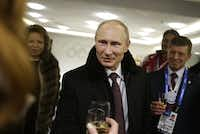Russian President Vladimir Putin (center) toasts guests in the presidential lounge as Deputy Prime Minister Dmitry Kozak (right) looks on following the opening ceremony.DAVID GOLDMAN - AFP/Getty Images
