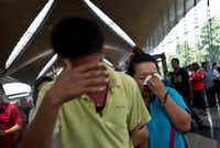 A woman breaks down while leaving the reception center for families and friends at Kuala Lumpur International Airport after a Malaysian Airlines Boeing 777 lost contact with air traffic control during a flight to Beijing. Malaysia and Vietnam led a search Saturday for a plane that carried 239 people.MANAN VATSYAYANA - AFP/Getty Images