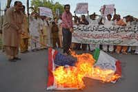Pakistani civilians burned Indian and U.S. flags after the airport attack. The Karachi assault may discourage foreign investment at a time when Pakistan's economy is ailing.( SS Mirza  - Presse )