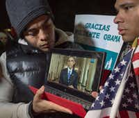 A supporter held a tablet in front of the White House streaming President Barack Obama's address on immigration reform Thursday.(PAUL J. RICHARDS - AFP/Getty Images)