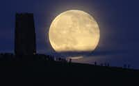 A full moon rose behind Glastonbury Tor on Monday as people gathered to celebrate the summer solstice in Somerset, England. (Matt Cardy/Getty Images)