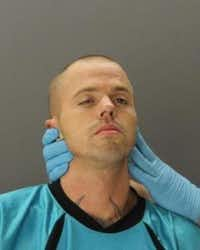 Jason Lee Smallwood had to be restrained for his mug shot.