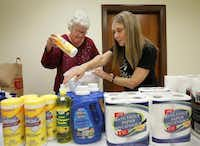 Volunteers Maunette Lively and Peggy Marquez put together care bags for clients.Staff photo by BRAD LOPER