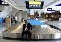 Chauffeur Roger Hastings waited alone at baggage claim in Terminal A to pick up a passenger during the flight delays Tuesday at Dallas/Fort Worth International Airport. The airline fared better Wednesday but was hampered by weather.