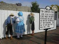 "Children dressed as Tom Sawyer and Becky Thatcher signing the famous white picket fence in Hannibal, Mo., that figured in Mark Twain's ""The Adventures of Tom Sawyer."""