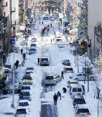 People cleared snow from parked cars in the Chinatown neighborhood of New York on Sunday, but there were other obstacles to overcome after a blizzard that set a new single-day snowfall record in Washington and New York City.( Peter Morgan  -  The Associated Press )