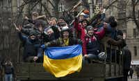 Protesters celebrated the dismissal of President Viktor Yanukovych as they rode through Kiev on Saturday. Yanukovych appeared on television in a pre-recorded interview and declared that he was still the nation's legitimate leader.(Darko Bandic - AP)