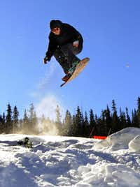 A snowboarder takes off on the opening day at  Arapahoe Basin in Colorado. A-Basin is part of a group of resorts called the Gems; the $20 Colorado Gems Card lets you buy one lift ticket and get another free at any of the eight resorts.