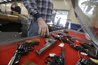 In this Friday, Feb. 6, 2015 photo, a dealer arranges handguns in a display case in advance of a show at the Arkansas State Fairgrounds in Little Rock, Ark.