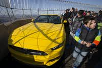 People walk past the all-new 2015 Mustang convertible as it's revealed by the Ford Motor Company on the 86th floor observation deck during the New York International Auto Show, Wednesday, April 16, 2014, in New York. (AP Photo/John Minchillo)John Minchillo - AP