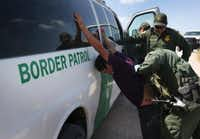U.S. Border Patrol agents detain undocumented immigrants after they crossed the border from Mexico into the United States in McAllen last August. (John Moore/Getty Images)