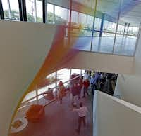"Visitors touring the new Resource Center passed under Gabriel Dawe's string-art piece ""Plexus"" during Saturday's open house. (Nathan Hunsinger/Staff Photographer)"