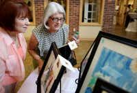 Sisters Cindy Gee (left) and Sandy Conwell, whose mother, Clara Smith, has Alzheimer's disease and lives in the community, looks at art during a silent auction for pieces of art at the Silverado Valley Ranch Memory Care Community in Irving on Tuesday. Their father, who is now deceased, had Alzheimer's. (Andy Jacobsohn/The Dallas Morning News)