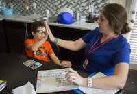 Jacob Casablanca (left) high-fives speech therapist Elizabeth Price during their session Monday, July 27, 2015 in Hurst, Texas. Jacob, 7, is autistic and suffers from speech delays. He receives weekly therapy at his home, part of a state program that could be cut as lawmakers in Austin look to trim $350 million in spending. (G.J. McCarthy/The Dallas Morning News)