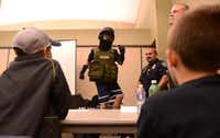 Ryan Lynch, 11, tries on Rowlett S.W.A.T. gear during the first youth police academy. The first of two week-long ÒacademiesÓ was geared toward fifth- through- eight grade students interested in exploring law enforcement careers.