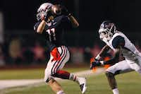 Flower Mound Marcus junior wide receiver Jack Cushing (11) grabs a catch as Ryan senior defensive back Randalle Williams (8) closes in during the Oct. 11.