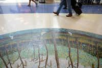 Airport patrons walk past Cypress Trees by Arthello Black.(Rose Baca - neighborsgo staff photographer)