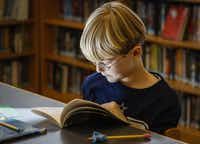 Elementary student David McAtee, 7, reads a book in the library at the school.(Staff photo by JIM TUTTLE - DMN)