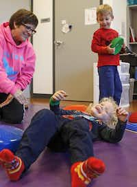 Physical education teacher Tracy Cossey (left) laughs with primary school student Jack Dyer, 4, as Michael Nadeau Jr., 4, looks on in the motor skills development lab at the Alcuin School in Dallas. The private school is seeking a rezoning which would allow them to add 100 more students in grades 10 to 12. Residents in the Hillcrest Forest Neighborhood Association are opposed to the request, saying it would increase traffic along an already narrow street( Staff photo by JIM TUTTLE  -  DMN )