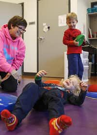 Physical education teacher Tracy Cossey (left) works with primary school student Jack Dyer. Fellow 4-year-old Michael Nadeau Jr. picks up a disc in the motor skills development lab at the Alcuin School.(Jim Tuttle - Staff Photographer)