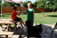 Allyson Hendrickson high-fives her son, Cade, in the family's backyard in Flower Mound. For seven years, Hendrickson, who is currently in hospice care, has kept a blog detailing her experience with ovarian cancer and thoughts about her three boys. She is also the first recipient for a fledgling foundation in her honor dedicated to granting the wishes of mothers with terminal illnesses.( Photo by ROSE BACA  -  neighborsgo staff photographer )