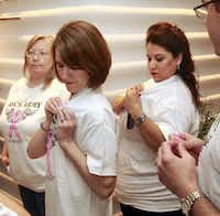 Katie Lackey (second from left) and Kim Collum put pink ribbons on their Amy's Army T-shirts in Fort Worth on Thursday. The team, from the law firm Cantey Hanger, is running to support a colleague recently diagnosed with breast cancer.