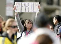 Justine Franco of Montpelier, Vt., holds up a sign near Copley Square in Boston looking for her missing friend, April, who was running in her first Boston Marathon.(Winslow Townson - The Associated Press)