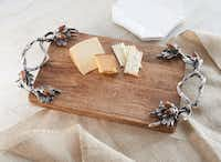Nuts to you Perfect for serving cheese or appetizers is a mango wood serve board accented with cast aluminum, oak leaf clusters and wooden acorn details. $78.95 at La Foofaraw, Plano