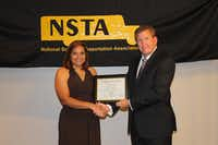 Angie Ortiz receives a certificate from Tim Flood, president of the National School Transportation Association, after finishing third at the 2015 School Bus Driver International Safety Competition.(Photo submitted by ANGIE ORTIZ)
