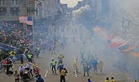 Moments after the first explosion near the finish line of the Boston Marathon, smoke is seen in the background where a second explosion occurred, Monday, April 15, 2013. (David L. Ryan/The Boston Globe)  NO SALESDAVID L. RYAN - NYT