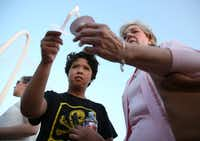 Linda Roden (right) lights Mary Ann Munoz's candle during a vigil honoring Antoinette Brown in Dallas on Memorial Day. (Rose Baca/The Dallas Morning News)