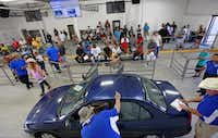 auctioneer assistants gather around a 2001 mitsubishi mirage as they prepare the car for auction