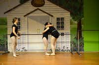 Carlee Baladez gets a hug from Carly Buchanan, 16, while Darby Watson, 12, looks on, during practice.( ROSE BACA/neighborsgo staff photographer )