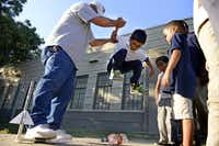 Employee John Sanchez helps Jaiden Martinez, 6, jump on a Coca-Cola bottle to release a rocket after school at the Bataan Community Center, part of the West Dallas Community Centers, in Dallas.( ROSE BACA  - neighborsgo staff photographer)