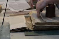 The Book Doctor's Christopher Lee makes sure an old Bible's pages are in order. A majority of the books restored by The Book Doctor are family bibles.