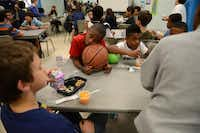 D.J. Baptiste, 10, rests his head on a basketball during snack time at the Boys and Girls Clubs of Collin County's Plano branch.(Rose Baca - neighborsgo staff photographer)