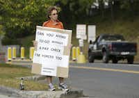 Maureen Flanagan, a government employee on furlough from her job at the U.S. Military Academy at West Point, N.Y., protested the federal shutdown outside an entrance to the academy Wednesday.