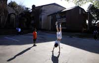 Jaylen Moore watches Austin Collins do a handstand at the Champions of North Dallas apartments, off the Dallas North Tollway between Addison Airport and the Bush Turnpike.
