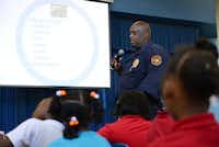 Lancaster ISD police officer Raymond Dyson speaks to students at Rolling Hills Elementary about types of bullying. The district and police department have led an anti-bullying campaign for four years and are now hosting school-wide assemblies to increase awareness.(ROSE BACA)